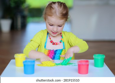 Laughing little child, blonde artistic toddler girl painting and drawing with colorful finger paints indoors at bright room at home or kindergarten.