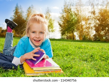 laughing little girl with books in park