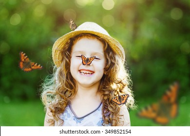 Laughing little girl with a butterfly on his nose. Happy childhood concept.