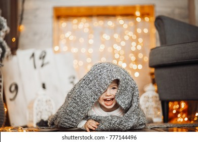 Laughing little girl hides under grey blanket on the floor