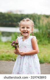 Laughing little girl holding flowers in a park
