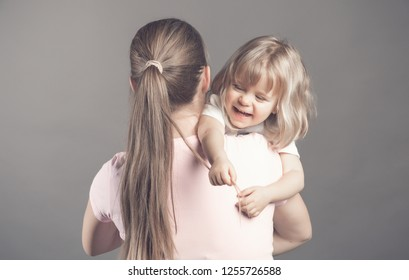 Laughing little girl looks happy in mother's arms Beautiful baby girl pulls mom's hair and smiling. Woman holding her daughter staying on the grey background. Rear veiw. Happy family and love concept