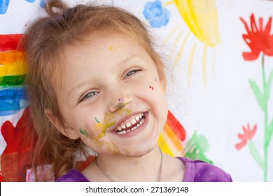 laughing little girl with painting