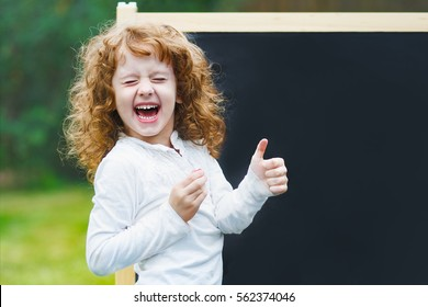 Laughing little girl showing white teeth, closed her eyes  and make gestured thumbs up, near school board.
