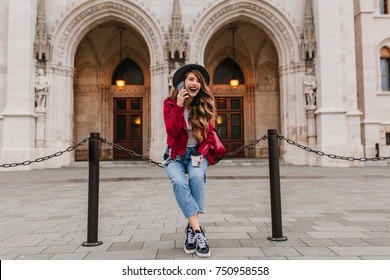 Laughing long-haired girl in jeans and red jacket sitting in front of old beautiful museum. Outdoor photo of pretty curly lady talking on phone near european church.