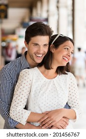 Laughing loving young couple in an urban street standing in a close embrace with the man hugging his wife from behind as they smile happily