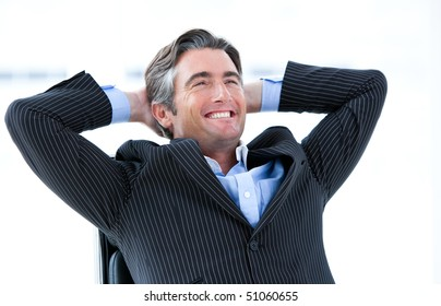 Laughing male executive thinking about his success in his office