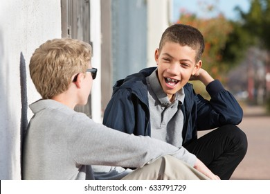 Laughing male teenager with braces beside friend sitting against wall outside