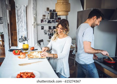 Laughing male and woman cooking together at kitchen and talking.