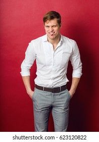 Laughing man in classic  white shirt posing in studio on red background. Hands in pockets.