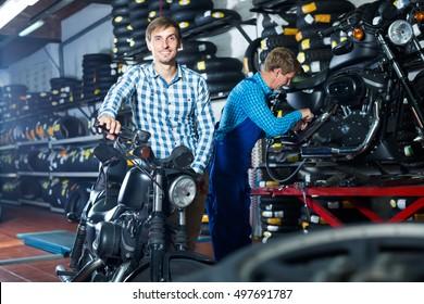 Laughing man customer holding his motorcycle at maintenance point
