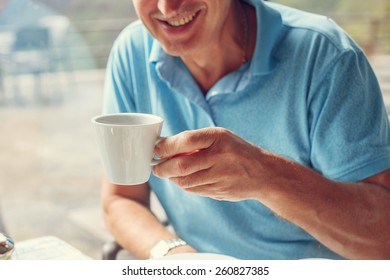 Laughing man have a lunch time and drinks his coffee