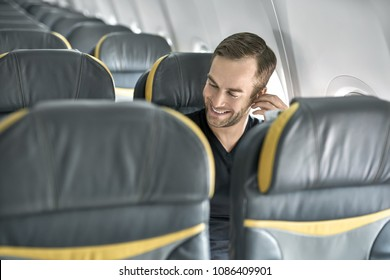 Laughing man sits in the airplane next to the window. He wears a black T-shirt, blue jeans and wireless headphones. Guy holds the left hand on the headphone. Closeup. Horizontal.