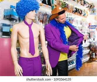 Laughing man is staying with comically dressed dummy in the shop.
