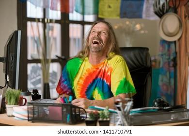 Laughing man in tie dye shirt at his desk
