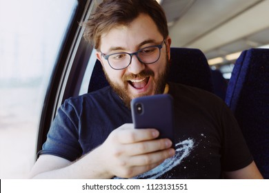 Laughing man in a train holding smartphone