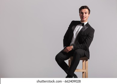 laughing man in tuxedo is sitting on chair on grey background