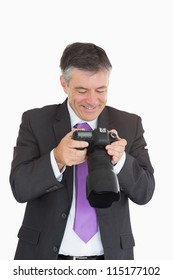 Laughing man viewing photos which on digital camera