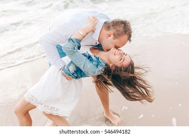 laughing man and woman on beach. developing hair and kiss. couple in love