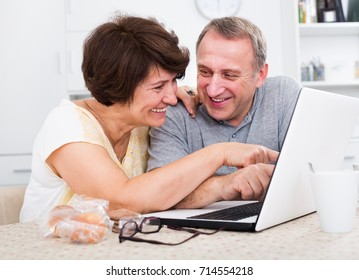 Laughing mature man and woman discussing while looking at the laptop together at the home. Focus on woman