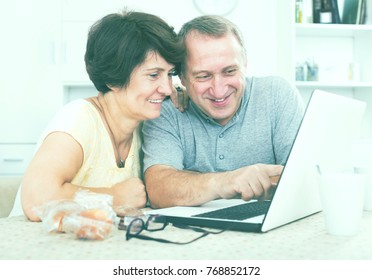 Laughing mature man and woman discussing while looking at the laptop together at home. Focus on man