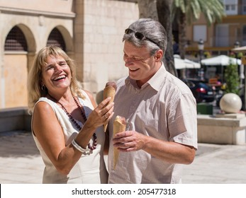Laughing mature senior couple eating ice cream together while he try to steal her ice cone on a hot summer day as they stand in a tropical town square