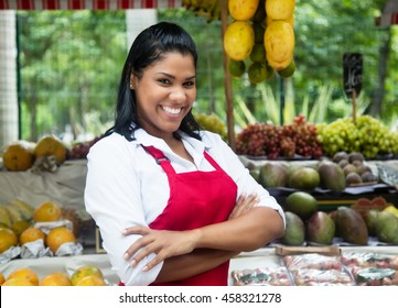Laughing mexican saleswoman with tropical fruits on farmers market