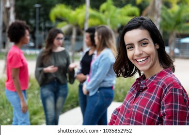 Laughing mexican young adult woman with girlfriends outdoors in the summer in the city