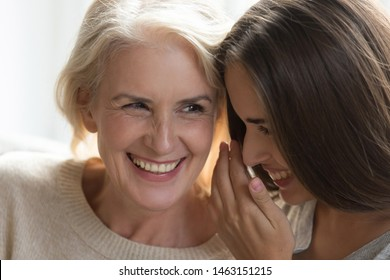 Laughing middle aged mother daughter gossiping sit close to each other spend enjoy time together, grandmother adult granddaughter best friends, intimates trusted person, love devotion, close up image