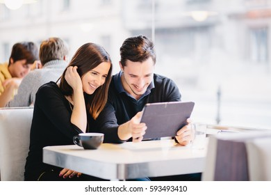 Laughing Millennial couple in love looking at photos tablet coffee shop