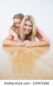 Laughing mother and daughter resting on the floor