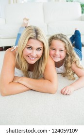 Laughing mother and daughter resting on the white carpet