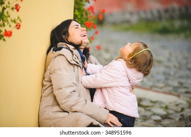 laughing mother and daughter in street