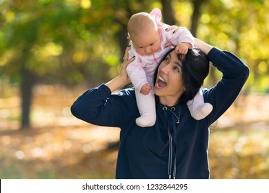 Laughing mother giving her baby daughter a piggy back ride as they walk together through a colorful autumn forest