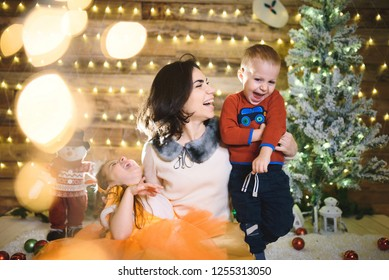 laughing mother with son and daughter in christmas lights