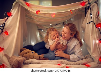 Laughing Mother And Young Daughter Having Fun In Homemade Camp In Child's Bedroom At Home - Shutterstock ID 1977379046