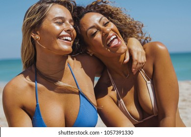 Laughing multiracial women in bikini embracing and having fun while chilling on sandy beach of ocean in bright sunshine.