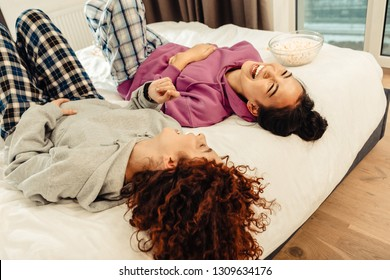 Laughing out loud. Couple of women laughing out loud while speaking with each other lying in bed