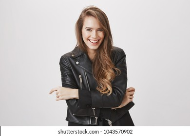 Laughing out loud in this beautiful spring day. Portrait of attractive urban girl with blond hair in leather jacket holding hands on chest, chuckling, looking at camera with happy playful expression