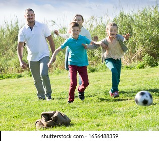 Laughing parents with two kids playing soccer on the green field