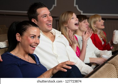Laughing people in a cinema or theater watching a movie or a play