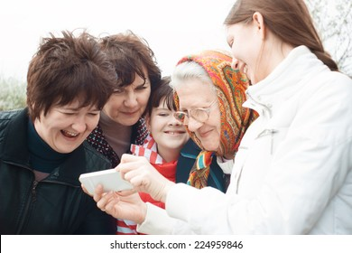 Laughing people look at mobile phone. Emotional group portrait. Women of all ages