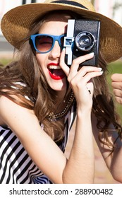 Laughing portrait of trendy and stylish woman make picture and look at camera,summer bright portrait of natural beauty.Smiling and happy woman look at camera,travel photo,summer accessories,jewelry