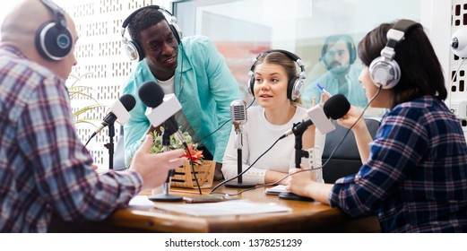 Laughing presenters of different nationalities in sound broadcasting station hosting live radio show