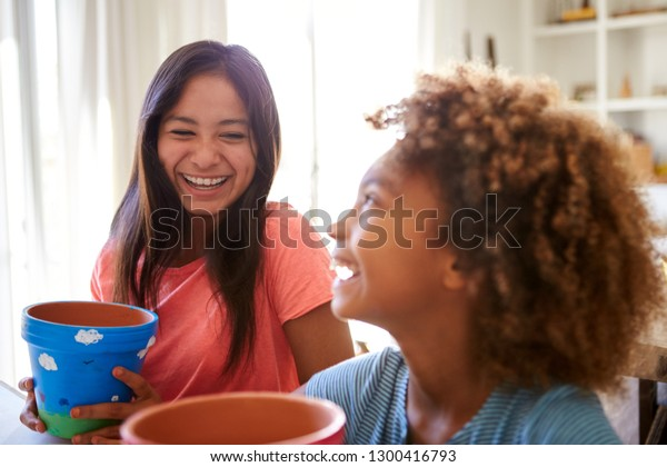 Laughing pre-teen girl and her older girlfriend holding plant pots that they've decorated with paints at home, selective focus, close up
