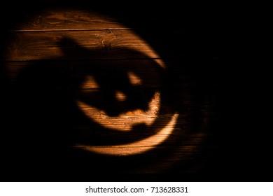 Laughing pumpkin Halloween Jack-o'-lantern of shadow on a dark wooden background