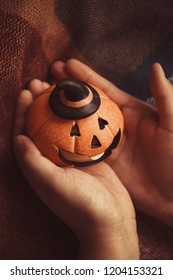 laughing pumpkin for Halloween on a warm cozy blanket in female hands Halloween symbol.