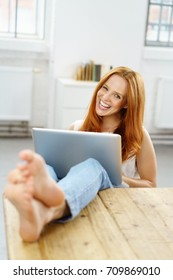 Laughing relaxed young woman with her bare feet on the table and a laptop balanced on her lap indoors in an apartment