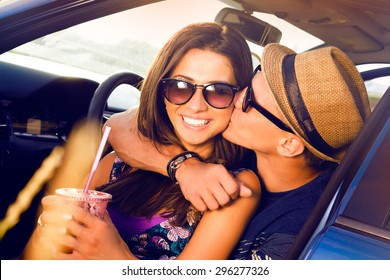 Laughing Romantic teenage hikers couple sitting on the hood of their car while out on a road trip.woman kissing boyfriend,smiling,outdoors.teen,purse,hat,Couple having fun on road trip on a summer day