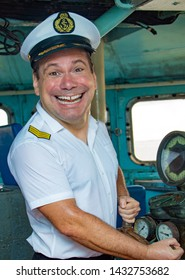 A laughing sailor officer in the uniform is steering the ship with a rudder. The funny captain standing in the wheelhouse of ship and looking to camera.
